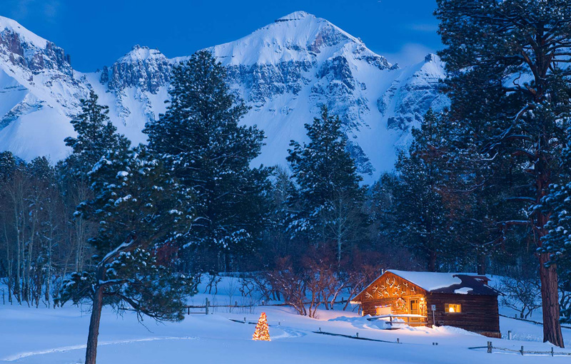 Rustic cabin with Christmas holiday lights nestled in ponderosa pines beneath the Sneffels Range, San Juan Mountains, Colorado