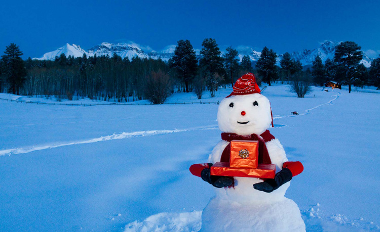 Snowman bearing presents in the San Juan Mountains in Colorado at dusk