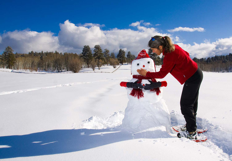 Woman building and decorating a snowman