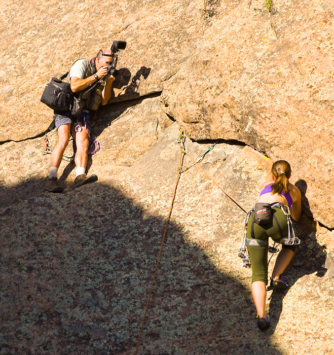 Production image of adventure photographer on a rock climbing shoot with his female climber at Tres Piedras, New Mexico