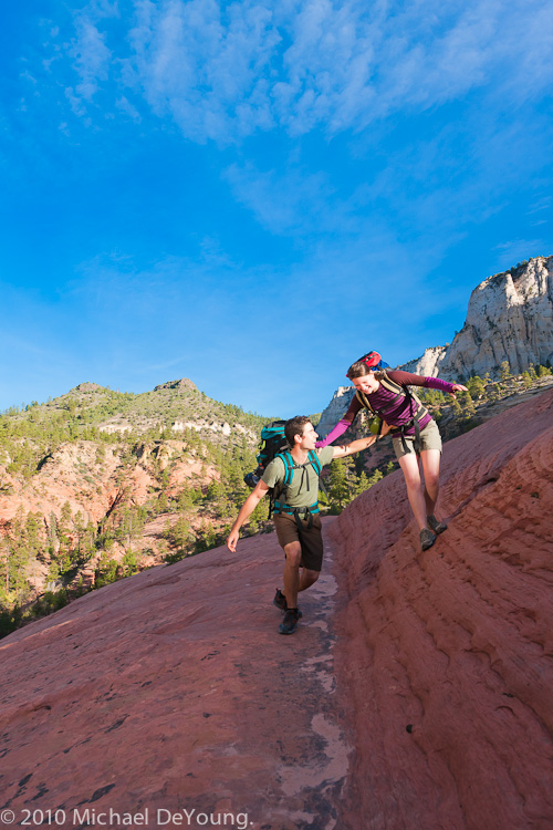 Young couple play around on the slickrock while heading toward the entrance to the Subway hike decent, Zion National Park