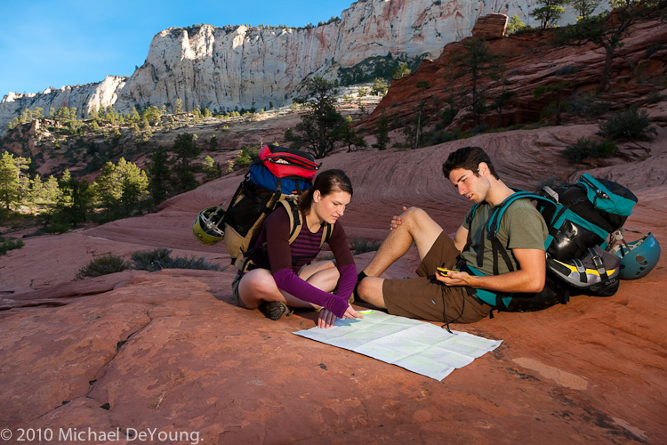 Young couple check the topo map at the beginning of the Subway hike ,Zion National Park