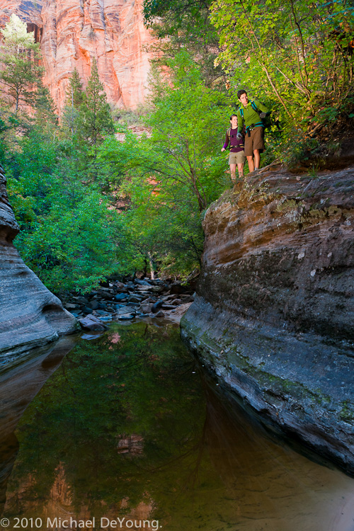 Young couple hike around deep pool of cold water in the Subway hike, Zion National Park