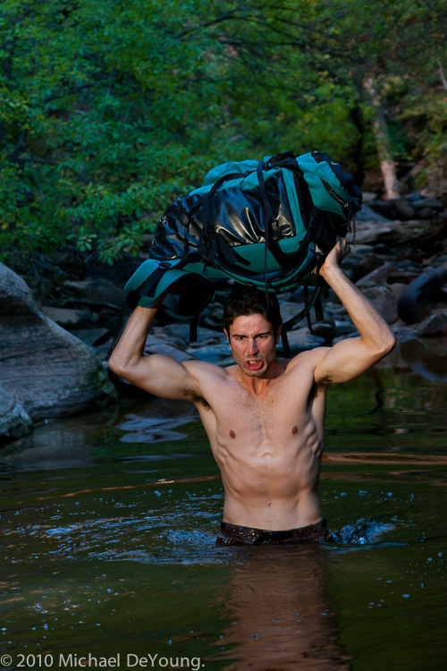Image of male hiker holding day pack over his head while crossing a waist deep pool of cold water in the Subway hike, Zion National Park