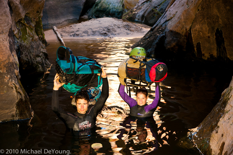 Young couple hold their backpacks over their heads while walking through deep pool in their wetsuits in the Subway, Zion National Park