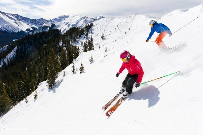 Skiers skiing down Hildalgo run off of Highline Ridge at Taos Ski Valley, New Mexico