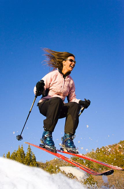 Woman skier in telemark ski gear taking air