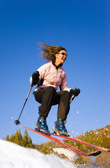 Woman skier in telemark ski gear taking air