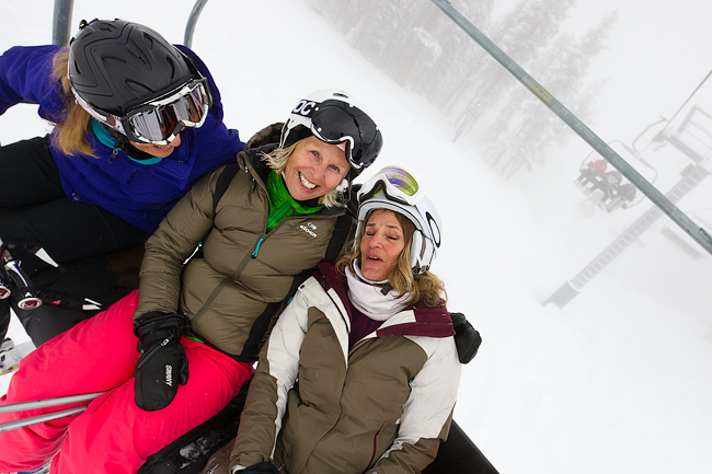 Ski lifestyle portrait of three mature women (baby boomer generation) skiers on chairlift at Taos Ski Valley, New Mexico