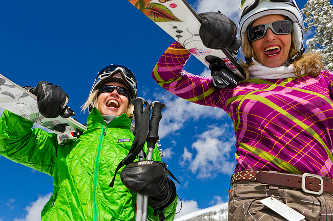 Lifestyle portrait of two mature women (baby boomer generation) walking and laughing with skis at Taos Ski Valley, NM
