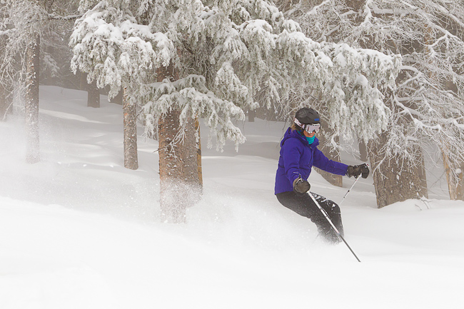Mature woman (baby boomer generation) skiing through powder at Taos Ski Valley, New Mexico