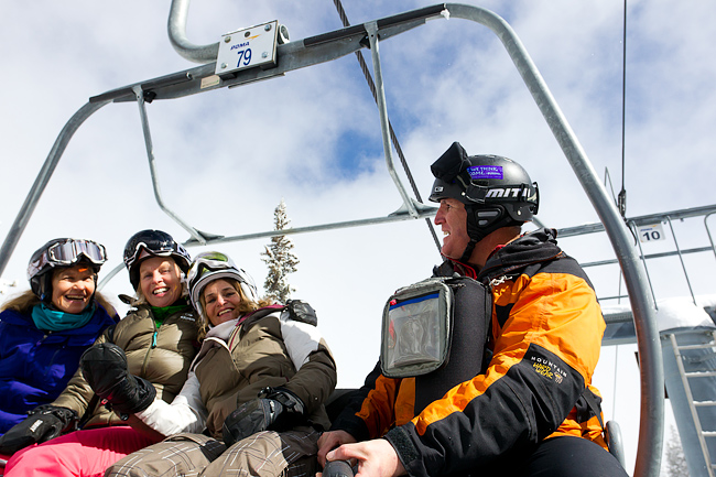 Photographer with three mature female (baby boomer) skiers on chairlift