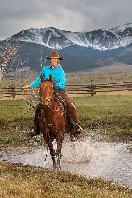 Westcliffe Colorado's Music Meadows Ranch woman owner riding a horse through a creek