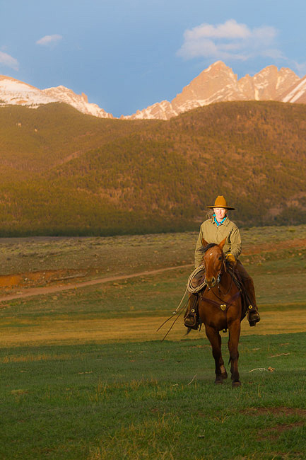 Westcliffe Colorado's Music Meadows Ranch woman owner riding a horse with Sangre De Cristo range in background