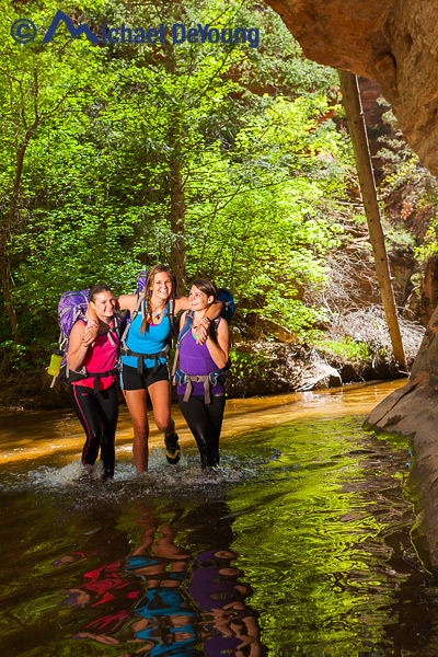 Three 20-something year old sisters having fun splashing through water in the middle of their Subway hiking adventure in Zion National Park