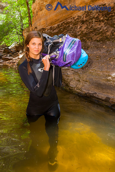 Young female hiker wading the first of several very cold pools of water in the Subway (Left Fork of North Creek) in Zion National Park