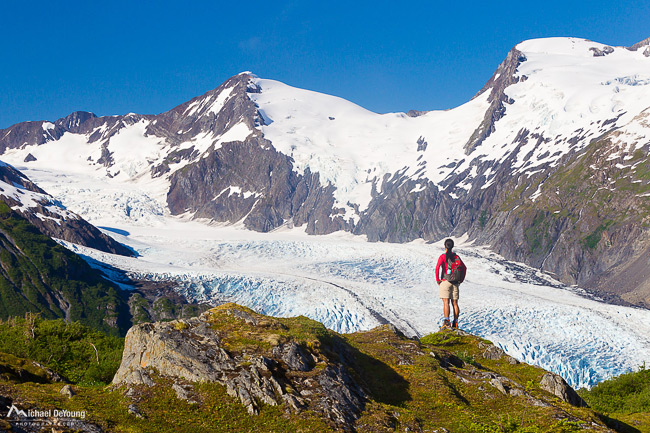 An Asian (Korean) female hiker on Portage Pass overlooking Portage Glacier in the Chugach Mountains, Chugach National Forest, above Prince William Sound, Southcentral Alaska