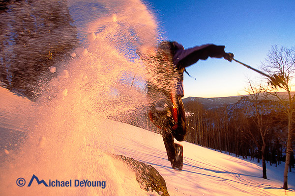 A snowshoer jumps at sunset up on Cedar Mountain, southern Utah