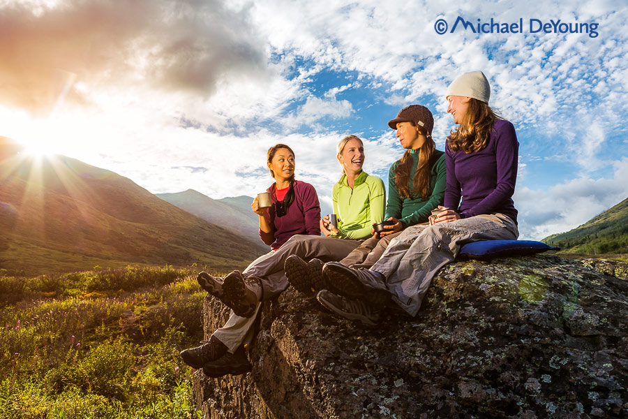 Four women camping and conversing with drinks at sunset, Chugach State Park, Alaska