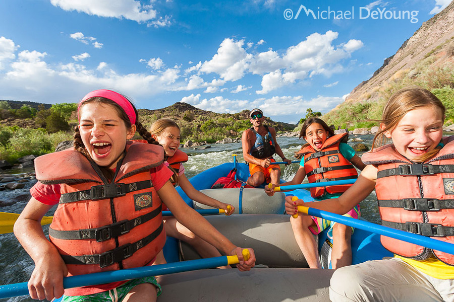 group of four 8 and 9 year old girls screaming through a rapid on guided raft trip, Racecourse Run, Rio Grande, New Mexico