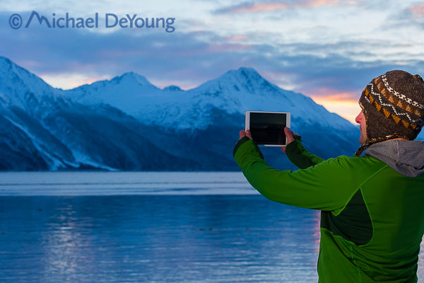 New Mexico Photographers Alaska Winter Lifestyle Photos - man taking sunset pictures with iPad tablet