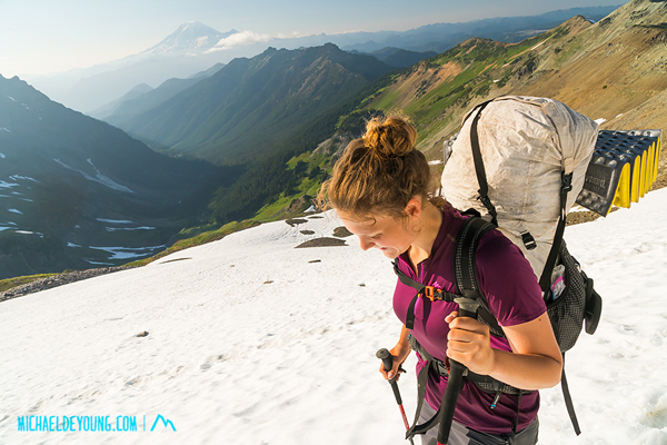 Juliette crossing  lingering August snows just below the Knife Edge with Mt. Rainer in the background
