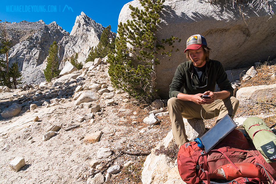 Emerson, a PCT Hiker, using a solar charger on his smartphone just below Kearsarge Pass