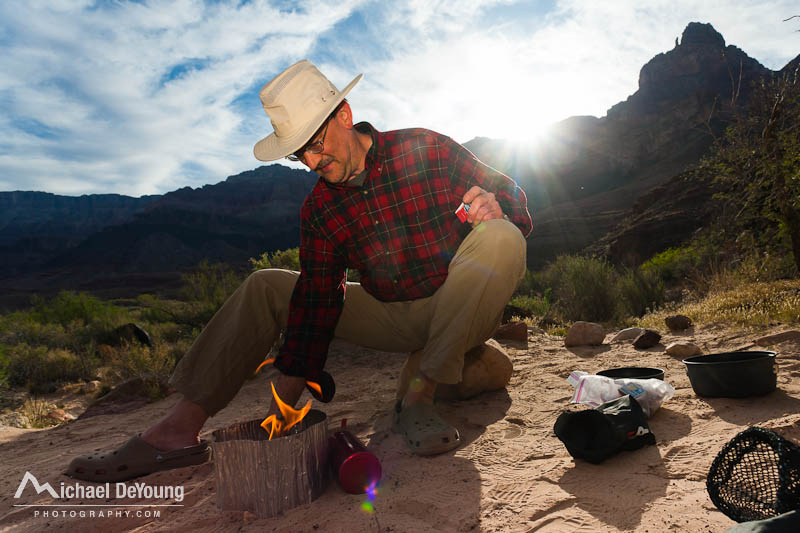 Mature male primes a backpacker stove at camp along the Colorado River in the Grand Canyon