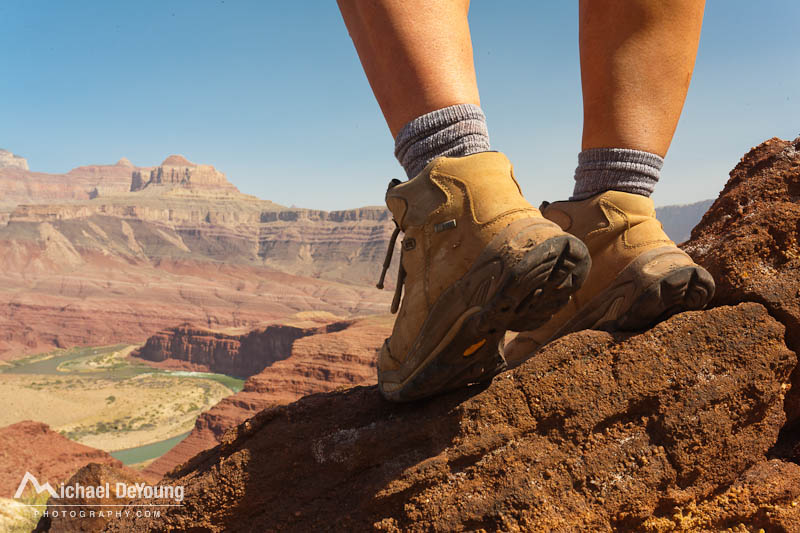 Close up portrait of woman hiking boots overlooking Colorado River along the Grand Canyon Escalante Route