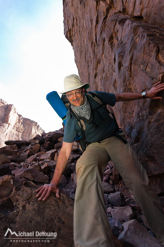 Mature male backpacker descending steep rockslide to get around Popago Creek on the Escalante Route of the Grand Canyon