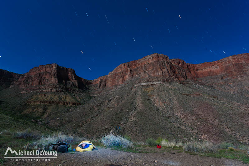 Mature male backpacker stargazing in his backpacking bivy sack above Hance Creek on the Tonto Trail, Grand Canyon National Park